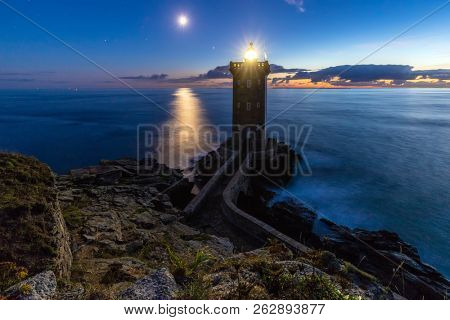 Romantic dusk scenery of lighthouse with moonbeam under the ocean, Kermorvan point, Brittany, France