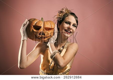 Halloween Pin Up Pretty Fashion Model On Pink Background. Girl In Yellow Dress With Pumpkin. Beauty