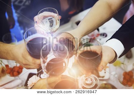 Lens Flare Short Of Male And Female Hands With Filled Glasses Of Wine Above The Restaurant Table. Dr