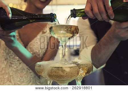 Smiling Happy Bride And Groom With Champagne Bottles Pouring Wine Into The Tower Glasses. Wedding Ch