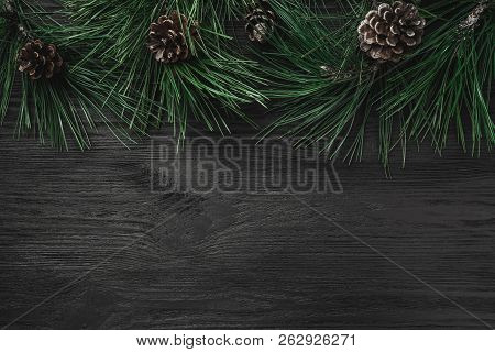 Christmas Card. Black Wood Background With Pine Branches And Pine Cones From The Top, Top View