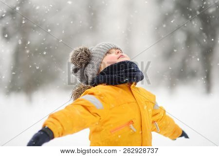 Cute Little Boy In Yellow Winter Clothes Walks During A Snowfall. Outdoors Winter Activities For Kid