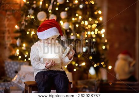 Cute Little Boy Wearing Santa Hat Opening A Christmas Gift. Portrait Of Happy Kid On Christmas Eve.