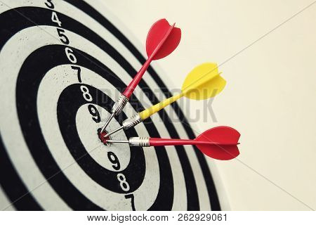 Side View Of A Dartboard With Three Darts In The Bulls Eye. Well-aimed Dart Throwing. A Triple Bulls