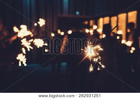 Close Up Of A Bengal Light At The Blurred Background Of People Standing With Burning Sparklers In Se