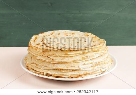 Pancakes On A Saucer On A Kitchen Towel. Many Pancakes Are Stacked. Thin Pancakes With Crispy Crust.