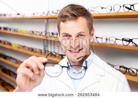 Optician. Selection of spectacle frames.A smiling optician in the optical salon.