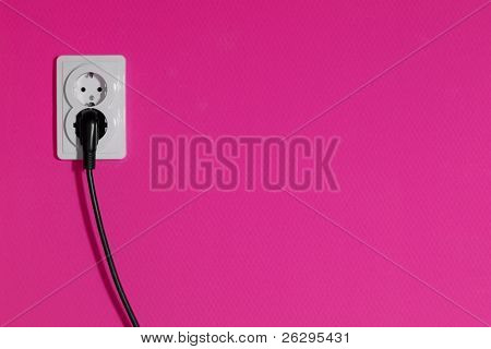 Cable connected into a power outlet on a pink wall