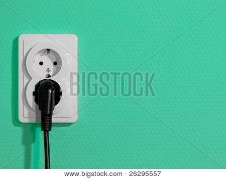 White electric socket on green wall