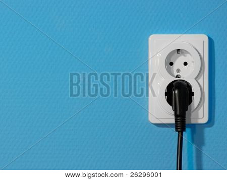 White electric socket on yellow wall