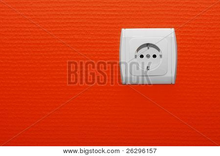 Electric socket with red wall background