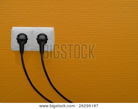 Two electric outlets on orange wall