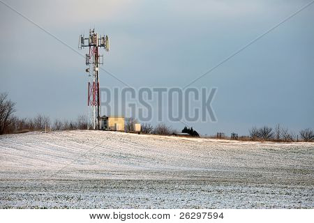 Telecommunication transmitter tower on a snowy field