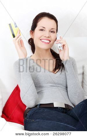 Front view portrait of a young beautiful smiling woman, sitting on a sofa, talking on the phone, rising up the credit card.