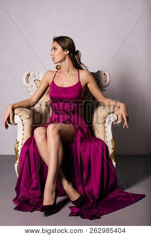 Magnificent Young Woman In Luxurious Dress A Is Sitting In A Chair Crossed Legs In A Luxury Apartmen