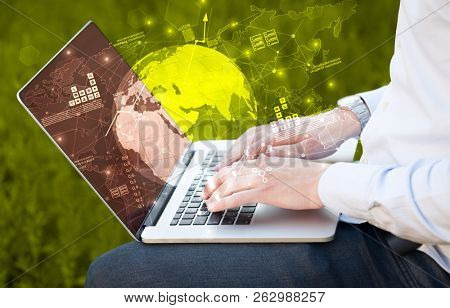 Hand using laptop with global reports and stock market change concept