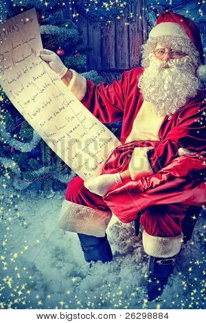 Santa Claus posing with a list of presents over Christmas background.