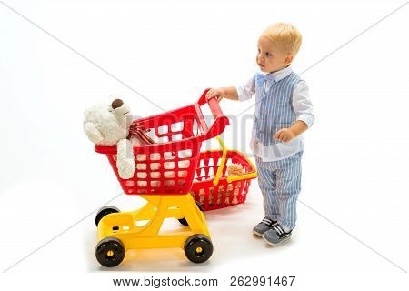 Little Boy Child In Toy Shop. Little Boy Go Shopping With Full Cart. Happy Childhood And Care. Shopp