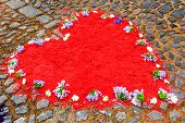 Red dyed sawdust heart shape on cobblestones decorated with purple flowers. poster