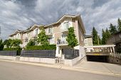 Residential apartment building with concrete driveway to underground garage. Residential condo building with fenced front yard on stormy sky background poster