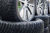 A close up of a lined winter studded wheels set outdoors. Close up of the studs and protectors on tires installed on the street. Winter tires positioned outdoors. Rows of exposed snow tires poster