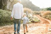 Grandfather and grandson walking at the farm poster