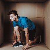 Young Man Doing Exercises in Little Cardboard Box. Sports and Healthy Lifestyle. Life in Little Cardboard Box. Uncomfortable Life. Personal Spase Concepts. Young Introvert. Man in Sportswear. poster