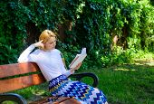 Literary critic. Lady pretty bookworm busy read book outdoors sunny day. Woman concentrated reading book in garden. Girl sit bench read book nature background. Woman prepare review about bestseller poster