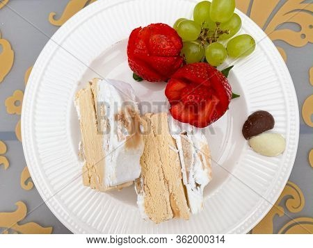 Dessert Plate With Caramel Ice Cream Cake, Red Rose Strawberries, Green Grapes And Chocolates In Hea