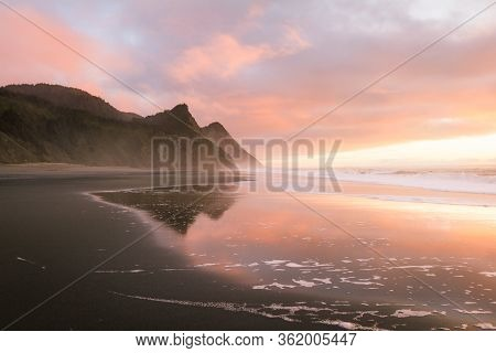 Gorgeous Sunset Scene In The Oregon Coast With Colorful Clouds Reflecting On The Wet Sand And Waves