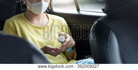 Asian Woman Passenger In Green Or Yellow Shirt With Surgical Mask Spraying Sanitizer Alcohol On Her
