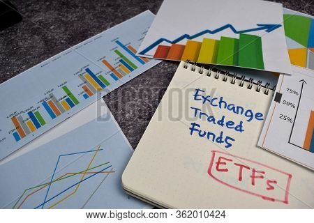 Etfs Write On A Book Isolated On Office Desk. Stock Market Concept