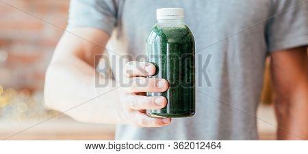 Healthy Nutrition. Balanced Detox Diet. Man Offering Bottle Of Fresh Organic Wheatgrass Juice.