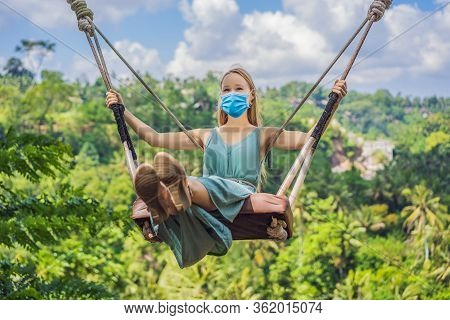 Young Woman In Medical Mask Swinging In The Jungle Rainforest Of Bali Island, Indonesia. Swing In Th