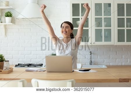 Young Attractive Woman Exulting Using Calculator And Laptop For Calculating.