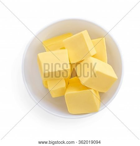 Butter Pieces In Bowl Isolated On White Background, Top View. Fresh Butter Chunks  Close Up