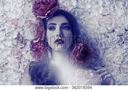 Beautiful young woman with gentle purple lilac make-up and peony flowers in her hair posing on a background of roses. Inspiration of spring and summer. Perfume, cosmetics concept.