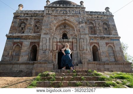 Blond Tourist Poses At The Tomb Of Sheesh Gumbad Tomb In Lodi Gardens In New Delhi, India