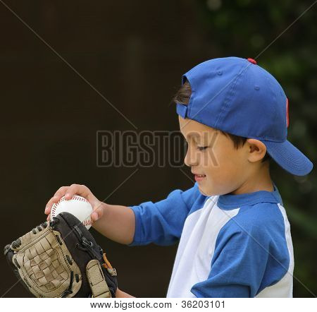 Hispanic Boy Playing With Baseball And Glove