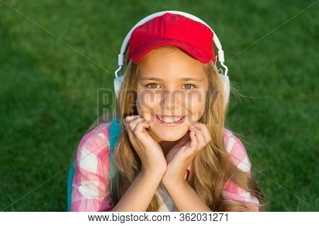 Everything Is Cool. Cool Kid Listen To Music On Green Grass. Happy Child Use Headphones Outdoors. Co