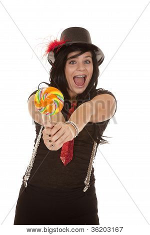 A teen girl in her jazzy outfit holding out a colorful sucker with a big smile on her face. poster
