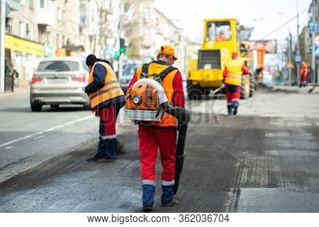 Worker With Leaf-blower, Cleaning Out The Dust For Better Asphalt Adhesion, During Tram Track Renewa
