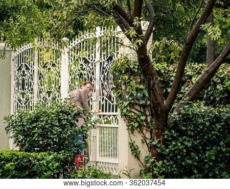 old woman opening a vintage iron gate on the front yard