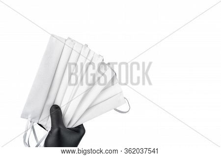 Hand In Black Protective Glove Holding Bunch Of Face Masks. Isolated On White Background. Copy Space