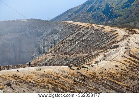 Ijen Volcano, Indonesia. Workers Mine Sulfur From The Crater Of The Volcano. Sulfur Mining.
