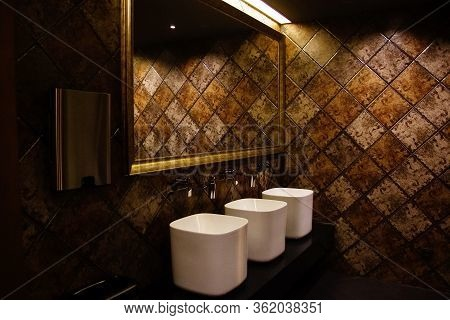Golden Brown Design Water Closet Room With Bronze Color Tile On A Wall And Big Mirror Three Sinks An