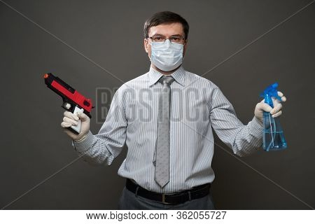 man dressed as a businessman posing with gun and hand sanitizer, studio shoot on gray background, medical face mask and protective gloves - concept of quarantine, cleaning and antivirus protection