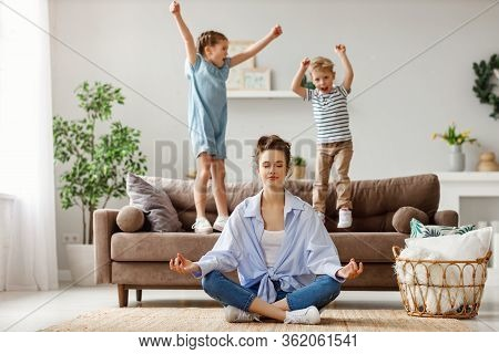 Happy Mother With Closed Eyes Meditating In Lotus Pose On Floor Trying To Save Inner Harmony While E