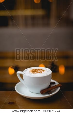 A Mug Of Hot Cappuccino With Cinnamon On A Saucer Stands On A Wooden Table In A Cafe.