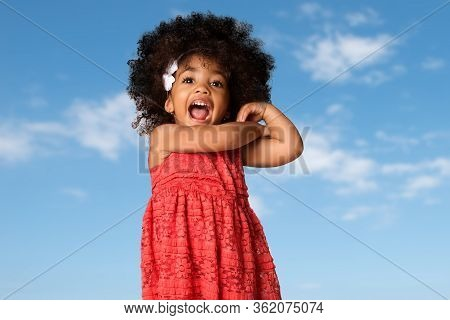 Portrait Of Cheerful African American Little Girl, Isolated Over Blue Sky Background